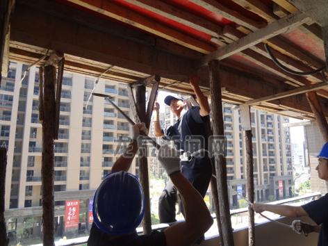 拆违人员对一处顶风抢建违法建筑进行拆除