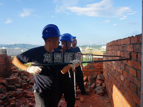 拆违工作人员对顶风抢建违建进行强制拆除