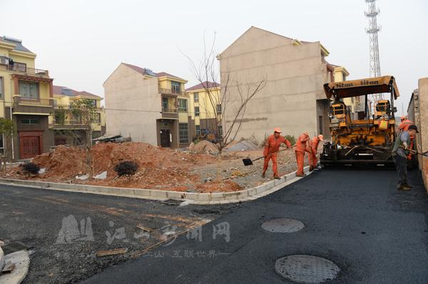 安置/12月27日,建设者正在麻车安置点铺设沥青路面。