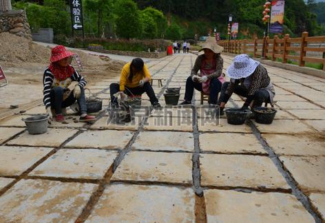 工人在景区石板路的缝隙里铺设鹅卵石