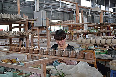 工人正在生产青瓷茶具