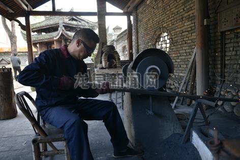 工人在用电动磨石为宝剑打磨