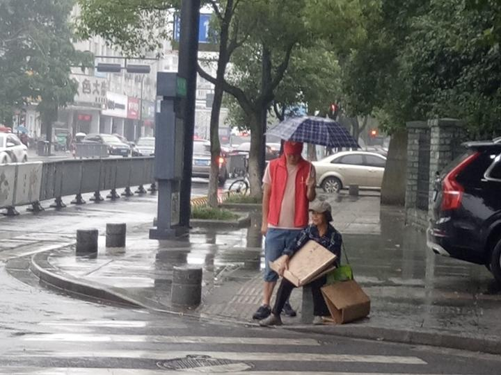 """大雨中的温暖 """"红马甲""""雨中为老人打伞"""