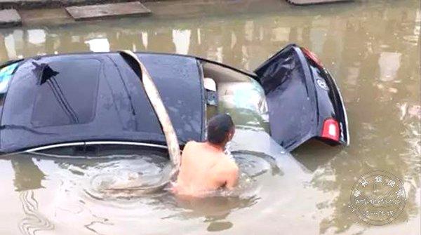 小车倒进河里村主任砸车救人