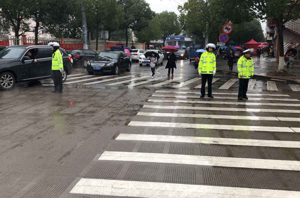 开学季,交警冒雨维护交通秩序