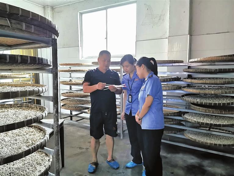 市场监管局工作人员对食品生产企业进行检查
