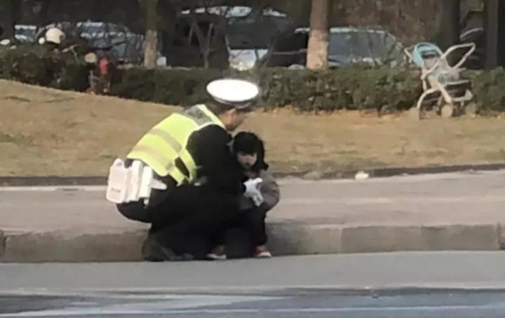 杭州真暖!小女孩蹲坐路边 萧山交警用身体为她挡风