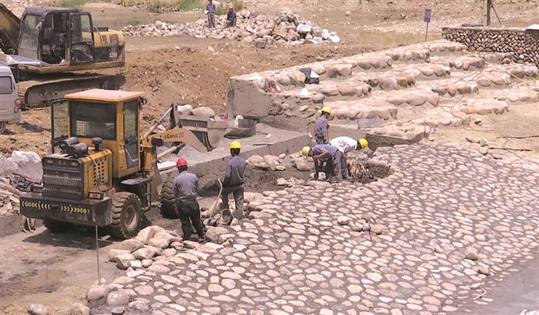 八都溪流域八都集镇上游段综合治理工程现场施工人员正忙于建设最后一座生态堰坝