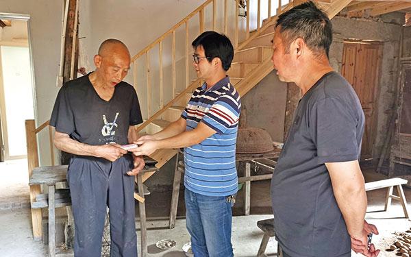 市慈善总会工作人员为低保户发放重建房屋受灾补助
