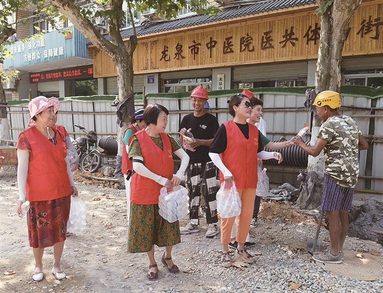 市退休教师协会的志愿者给在高温下坚持施工的工人们送防暑物品