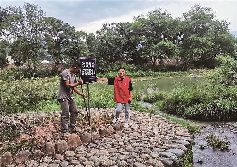 查田镇茶丰小学工作人员在溪边设立安全警示牌