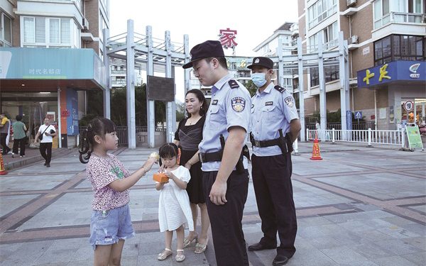 小女孩向中秋节坚守在岗位上的民警送月饼